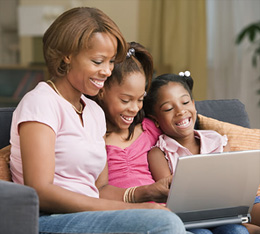 Mother and daughters smiling at laptop