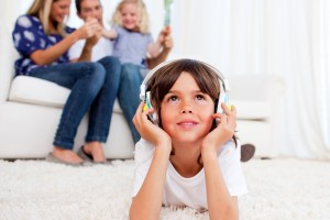 Boy-listening-to-music-with-family-in-background