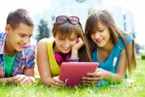 children viewing a tablet on grass