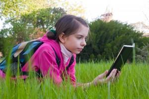 girl reading from an e-reader outside