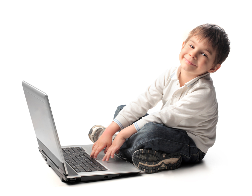 smiley elementary boy using laptop