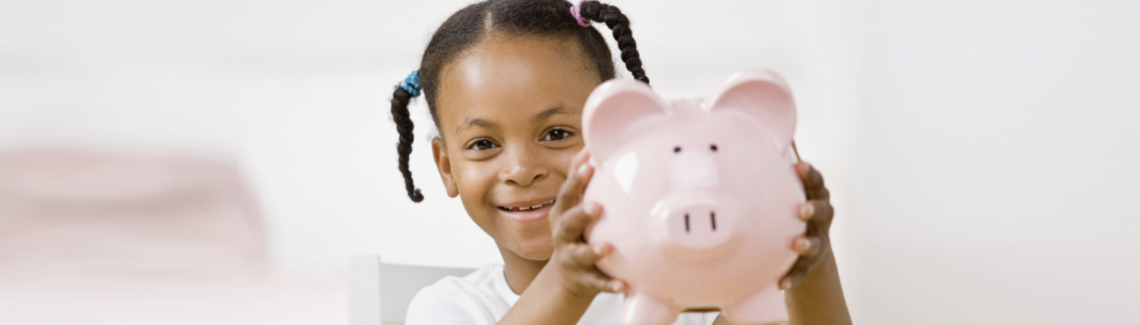 Responsible girl putting money into piggy bank for future savings