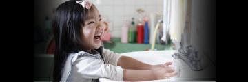 Little girl washing hands in a sink