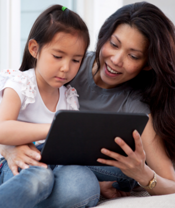mom helping a daughter with her tablet