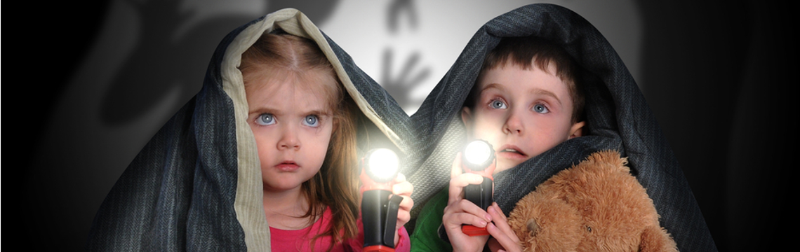 two kids with flashlight under covers