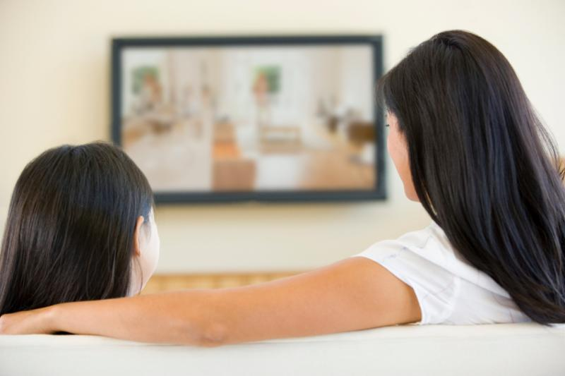 Child and parent watching TV