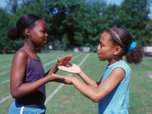 two girls outside clapping hands together