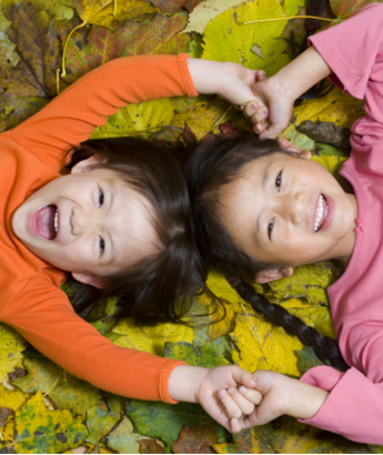 two young children lying in leaves holding hands
