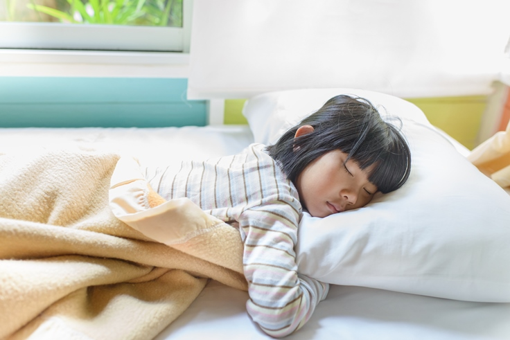 Young girl sleeping hugging a pillow