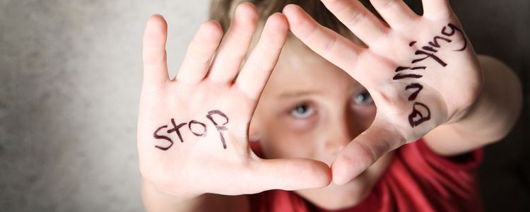 Young boy showing his hands, with the words 'stop bulling' painted on them