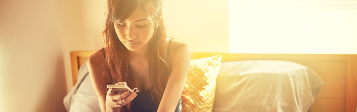 Young woman on her smartphone in golden sunlight