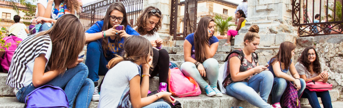Group of tweens sitting outside, many using cell phones, with backpacks