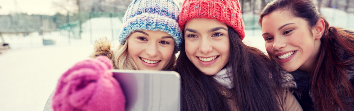 Three older teenage girls taking a selfie photo while standing outside in the snow