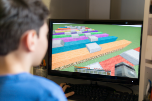 Young boy playing a video game similar to Minecraft