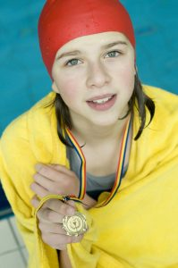 Young woman swimmer with a gold medal