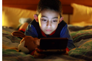 Young boy playing handheld video game device while lying on his bed