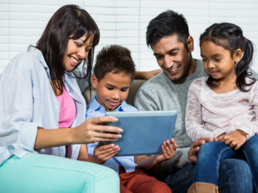 Family looking at a tablet computer together ad smiling
