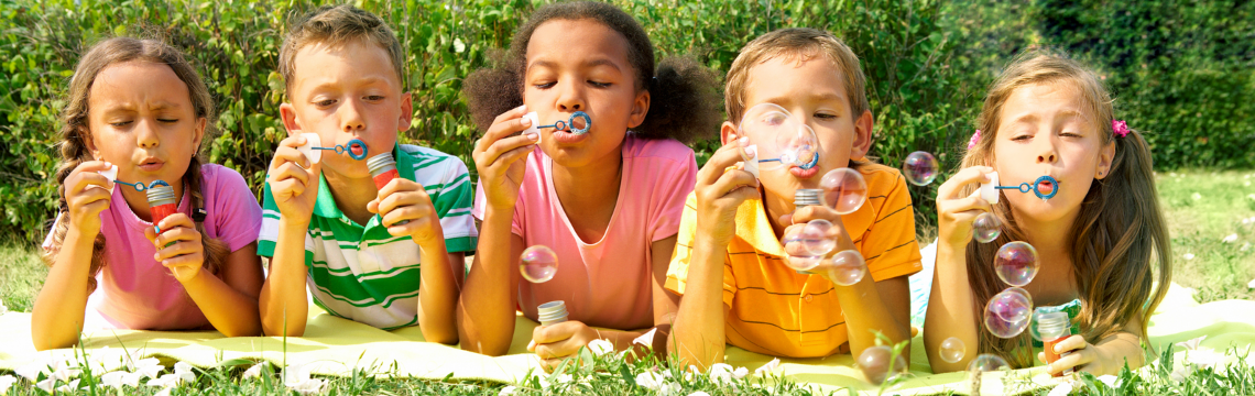 Children laying on the grass blowing bubbles