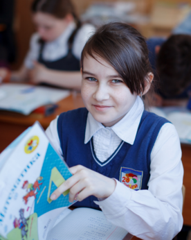 a young girl in a school uniform with a book