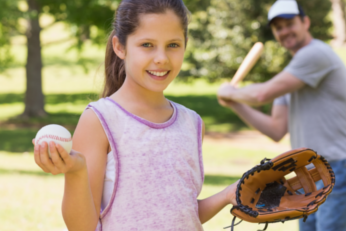 Tween girl holding a baseball with an adult male holding a baseball bat in the background