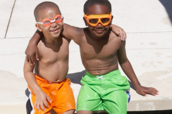 Two young boys wearing swimming goggles and sitting at the edge of a pool