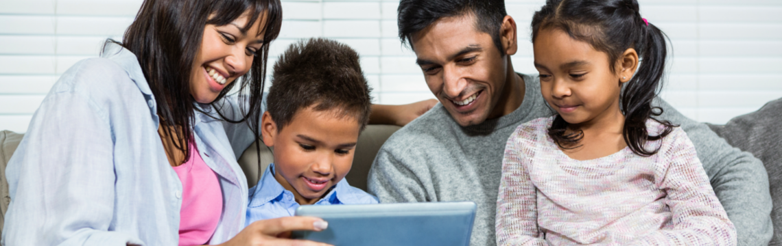 Family of four (two parents and two children) smile while holding and looking at a tablet computer