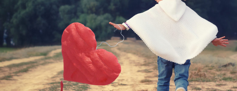 girl running with heart-shaped balloon