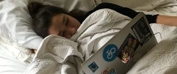 young woman watching laptop in bed