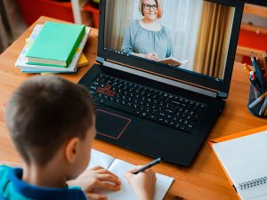 a child learning from a teacher over video from home