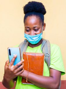 young student in mask checking phone