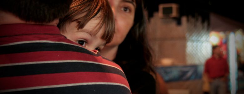 child peering over an adult's shoulder
