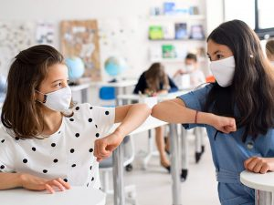 two tweens with masks elbow bump in class