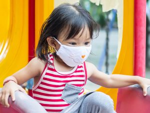 young child in mask at playground